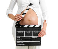 Pregnant woman hands holding clapper board on her belly. Isolated stock photography