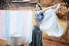 Pregnant woman hanging sheets on the rope for drying royalty free stock photography