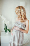 A pregnant woman. A happy pregnant woman in bedroom with flower royalty free stock photos