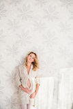 A pregnant woman. A happy pregnant woman in interior. near the wall royalty free stock photo
