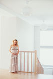 A pregnant woman. A happy pregnant woman. interior. stairs stock image