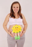 Pregnant woman has put the toy to the stomach Stock Photography