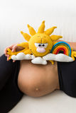 a pregnant woman has a toy on her stomach Royalty Free Stock Images