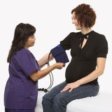 Pregnant woman having blood pressure checked. Royalty Free Stock Photography