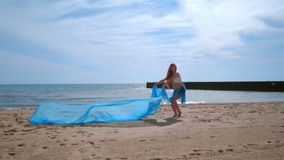Pregnant woman having fun with blue cloth flying in wind. Pregnant woman beach stock video