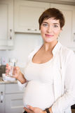 Pregnant woman having a glass of water Royalty Free Stock Photography