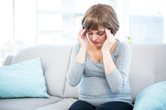 Pregnant woman having headache on couch Stock Images