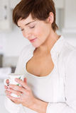 Pregnant woman having a hot drink Stock Photo