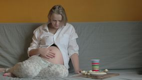 Pregnant woman having meal and relaxing at home stock footage