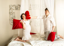 Pregnant woman having pillow fight with husband on bed with bald Stock Images