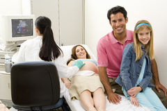 Pregnant woman having ultrasound scan with husband and daughter (9-11), smiling, portrait Stock Photo