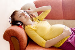 Pregnant woman with headphones stock images