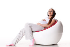 Pregnant woman with headphones Royalty Free Stock Images
