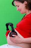 Pregnant woman headphones on her stomach Stock Photo