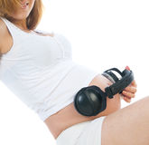 Pregnant woman with headphones on her stomach Stock Images