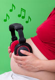 Pregnant woman with headphones on stomach Royalty Free Stock Photos