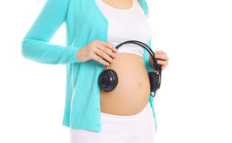 Pregnant woman and headphones Royalty Free Stock Photography