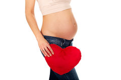 Pregnant woman with a heart pillow Royalty Free Stock Photos