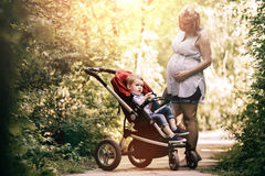 Pregnant woman with her child in pram Royalty Free Stock Photos