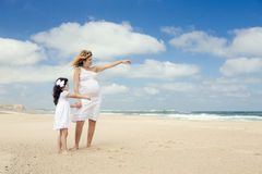 Pregnant woman and her daughter on the beach Royalty Free Stock Photography