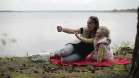 Pregnant woman and her daughter making selfie on on a picnic near the lake. stock video