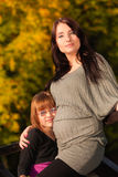 Pregnant woman with her daughter in park outdoor Royalty Free Stock Photo