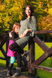 Pregnant woman with her daughter in park outdoor Stock Images