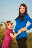 Pregnant woman with her daughter in park outdoor Royalty Free Stock Images