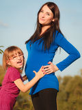 Pregnant woman with her daughter in park outdoor Stock Photography