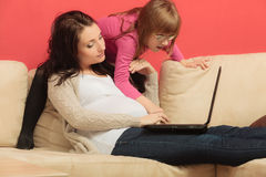 Pregnant woman and her daughter using laptop Stock Photography