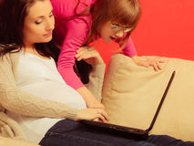 Pregnant woman and her daughter using laptop Royalty Free Stock Images