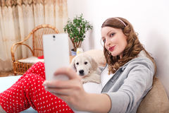 Pregnant woman with her dog at home Stock Photo