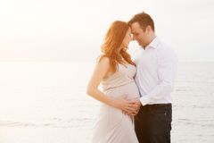 A pregnant woman with her husband on the beach Royalty Free Stock Photography