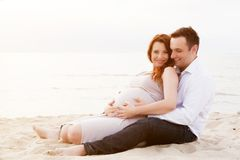 A pregnant woman with her husband on the beach Royalty Free Stock Image