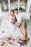 Pregnant woman with her husband in the bed Stock Image