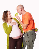 The pregnant woman with her husband and  green apple. The pregnant women with her husband love, care and with green apple  on the black background Stock Photos