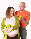 The pregnant woman with her husband and  green apple Stock Photo
