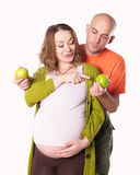 The pregnant woman with her husband and  green apple Stock Images