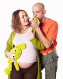 The pregnant woman with her husband and  green apple Stock Photography