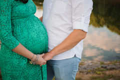 Pregnant woman and her husband in green dress. Royalty Free Stock Photo