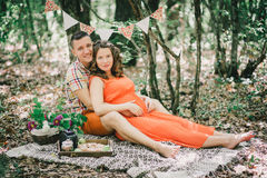 Pregnant woman with her husband having picnic in a forest Stock Photos