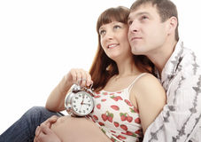 Pregnant woman and her husband holding alarm clock Royalty Free Stock Photos