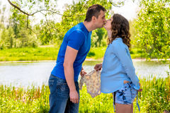 Pregnant woman and her husband kiss in the park Royalty Free Stock Photo