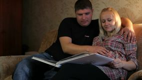 A pregnant woman with her husband looking photo album. stock video footage