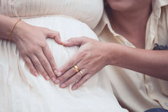 Pregnant woman and her husband making hand heart shape together Royalty Free Stock Photography