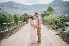 Pregnant woman with her husband on the mountains background Stock Photos