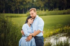 Pregnant woman and her husband in a park near the water hugging stock image