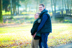 Pregnant woman with her husband in the park Stock Images