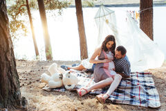 Pregnant woman with her husband at  picnic Stock Photo