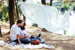 Pregnant woman with her husband at a picnic. Stock Photos